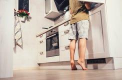 Niño pequeño en el intento de la cocina para encontrar algo en rifregerator imagen de archivo libre de regalías