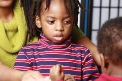 Niño pequeño en el medio de su familia Fotografía de archivo