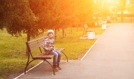 Niño pequeño en el parque del otoño que se sienta en un banco, Fotografía de archivo