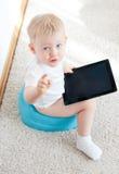 Niño pequeño en el potty con PC de la tableta imagenes de archivo