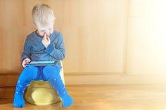 Niño pequeño en el potty con PC de la tableta en la alfombra blanca imagenes de archivo