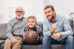 Niño pequeño en el sofá con el abuelo y el padre, animando para un juego de baloncesto y sosteniendo a Fotos de archivo libres de regalías
