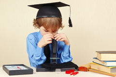 Niño pequeño en el sombrero académico que mira a través del microscopio su escritorio Imagen de archivo libre de regalías