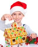 Niño pequeño en el sombrero de Papá Noel con la casa de pan de jengibre Imagen de archivo