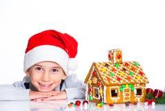 Niño pequeño en el sombrero de Papá Noel con la casa de pan de jengibre Imágenes de archivo libres de regalías