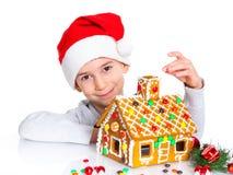 Niño pequeño en el sombrero de Papá Noel con la casa de pan de jengibre Fotos de archivo libres de regalías