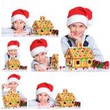 Niño pequeño en el sombrero de Papá Noel con la casa de pan de jengibre Fotos de archivo
