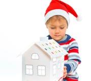 Niño pequeño en el sombrero de Papá Noel con la casa de pan de jengibre Imagen de archivo libre de regalías