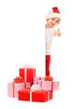 Niño pequeño en el sombrero de Papá Noel que mira a escondidas de detrás espacio en blanco Fotografía de archivo libre de regalías