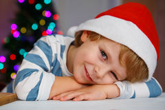 Niño pequeño en el sombrero de santa con el árbol de navidad y las luces Foto de archivo