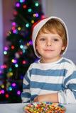 Niño pequeño en el sombrero de santa con el árbol de navidad y las luces Fotos de archivo