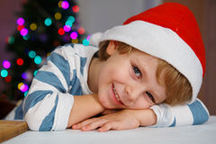 Niño pequeño en el sombrero de santa con el árbol de navidad y las luces Fotografía de archivo libre de regalías