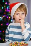 Niño pequeño en el sombrero de santa con el árbol de navidad y las luces Foto de archivo libre de regalías
