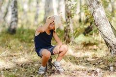 Niño pequeño en el sombrero que se sienta en un tocón en el bosque en el verano Fotografía de archivo