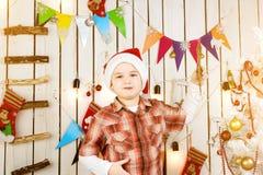 Niño pequeño en el sombrero rojo que sostiene el juguete del árbol de navidad Fotos de archivo