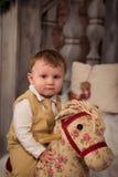 Niño pequeño en jugar con el caballo del juguete Imágenes de archivo libres de regalías