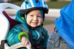 Niño pequeño en la bicicleta del asiento detrás del padre Imagen de archivo libre de regalías