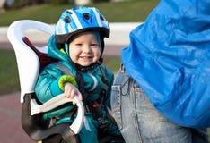 Niño pequeño en la bicicleta del asiento detrás del padre Fotos de archivo libres de regalías