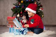 Niño pequeño en la Navidad, presentes de apertura Fotos de archivo