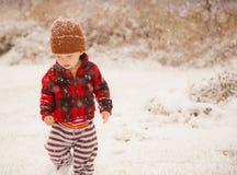 Niño pequeño en la nieve del invierno que cae Imagen de archivo