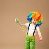 Niño pequeño en la peluca del payaso smilling y que juega con la primavera mágica Fotos de archivo
