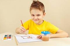 Niño pequeño en la pintura amarilla de la camisa con las acuarelas Imagenes de archivo