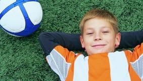 Niño pequeño en la reclinación uniforme del fútbol sobre el estadio de la hierba al lado del balón de fútbol Fútbol desde niñez Imágenes de archivo libres de regalías