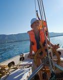 Niño pequeño en la rueda del barco de vela Fotografía de archivo