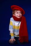 Niño pequeño en la sonrisa roja de la bufanda y de la boina Foto de archivo