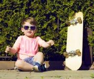 Niño pequeño en las gafas de sol que presentan con el patín adentro Fotografía de archivo