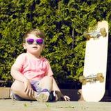 Niño pequeño en las gafas de sol que presentan con el patín adentro Fotos de archivo libres de regalías
