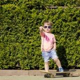 Niño pequeño en las gafas de sol que presentan con el patín adentro Imágenes de archivo libres de regalías