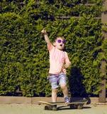 Niño pequeño en las gafas de sol que presentan con el patín adentro Foto de archivo