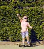 Niño pequeño en las gafas de sol que presentan con el patín adentro Fotos de archivo