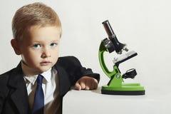 Niño pequeño en lazo Niño Niños Colegial que trabaja con un microscopio Muchacho elegante Fotografía de archivo