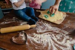 Niño pequeño en los vaqueros que mezclan la harina en la cocina en una tabla que hace un cierto lío imagenes de archivo