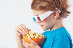 Niño pequeño en los vidrios 3D con el cuenco de palomitas Foto de archivo libre de regalías