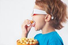 Niño pequeño en los vidrios 3D que come las palomitas Fotografía de archivo