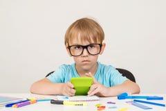 Niño pequeño en los vidrios que se sientan en el escritorio con las fuentes de escuela, haciendo la preparación en la tabla De nu fotos de archivo libres de regalías