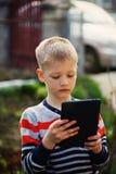 Niño pequeño en naturaleza con la tableta, retrato al aire libre Imágenes de archivo libres de regalías