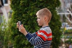 Niño pequeño en naturaleza con la tableta, retrato al aire libre Foto de archivo libre de regalías