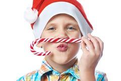 Niño pequeño en nuevo Year& x27; casquillo rojo de s con isola del bastón de caramelo de la Navidad Imagen de archivo