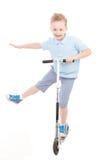 Niño pequeño en pantalones cortos y camisa con la vespa Fotografía de archivo