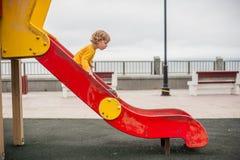 Niño pequeño en patio de la diapositiva del ` s de los niños Fotografía de archivo