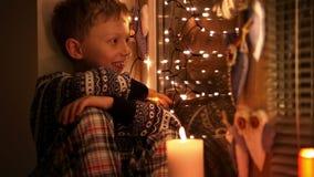 Niño pequeño en pijamas y asientos calientes del suéter en el alféizar que ríe durante el tiempo de la pre-Navidad metrajes