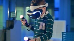 Niño pequeño en reguladores del movimiento del movimiento de la tenencia de las auriculares de la realidad virtual fotos de archivo