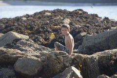 Niño pequeño en rocas de la playa en un día soleado Fotografía de archivo libre de regalías