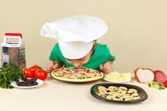 Niño pequeño en sombrero de los cocineros que huele la pizza cocinada Fotografía de archivo