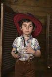Niño pequeño en sombrero de vaquero con el arma Foto de archivo