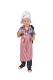 Niño pequeño en sombrero del cocinero del cocinero y cuchara grande a disposición Imágenes de archivo libres de regalías